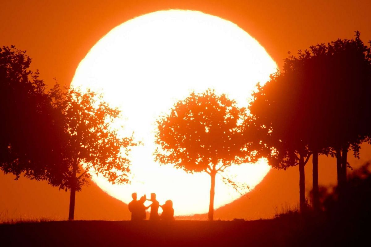 A picture made available 13 September 2016 shows people silhouetted against the setting sun in Hanover, Germany, September 13, 2016. PHOTO: EPA
