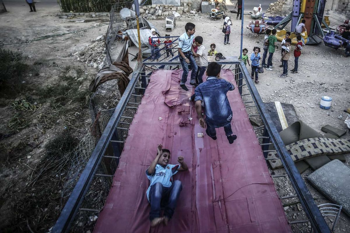 Syrian children playing on a trampoline during the second day of Eid Al Adha in Douma, outside Damascus, Syria, September 13, 2016. PHOTO: EPA