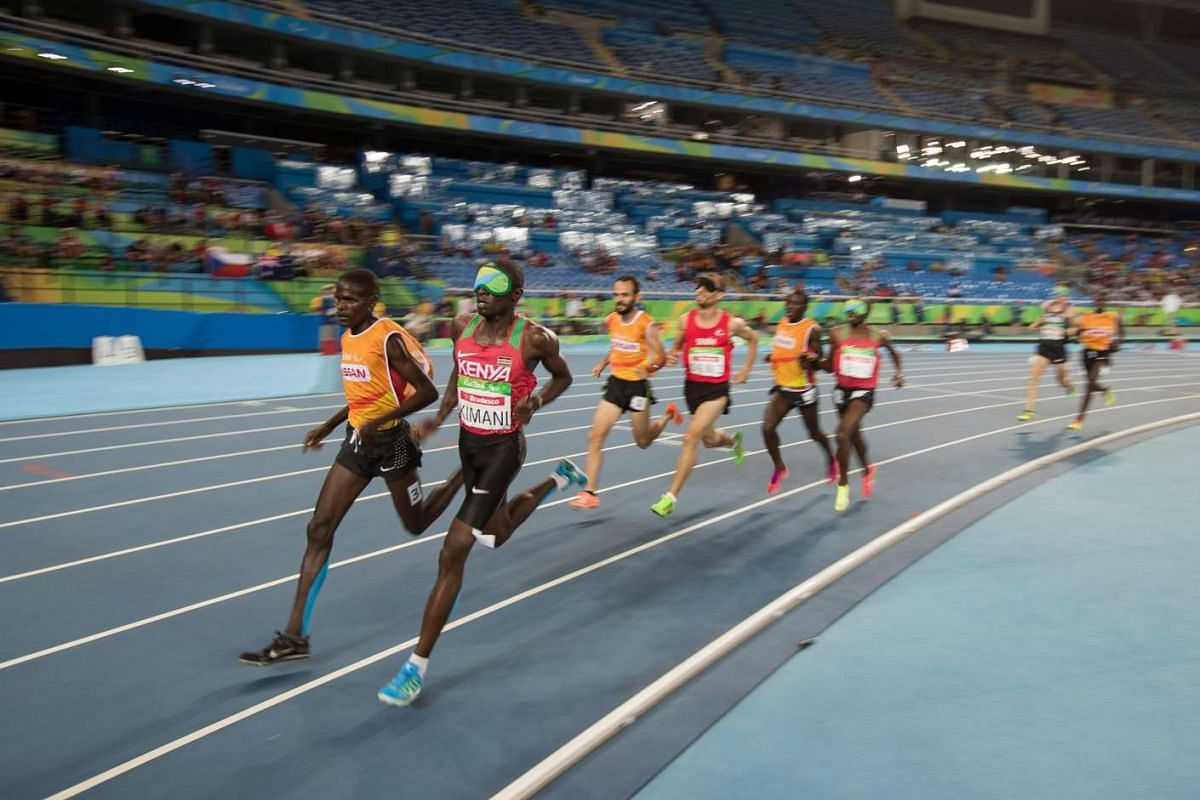 Samwel Mushai Kimani of Kenya with his guide James Boit leads the Men's 1500m final athletics event of the Rio 2016 Paralympic Games on Sept 13, 2016.