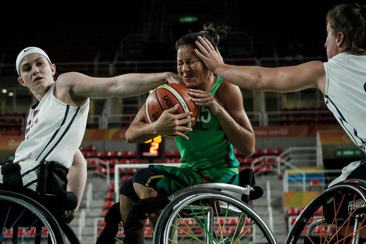The USA's Desiree Miller (left) and Gail Gaeng (right) block Brazil's Vileide Almeida during the women's wheelchair basketball quarterfinal in the Paralympic Games on Sept 13, 2016.