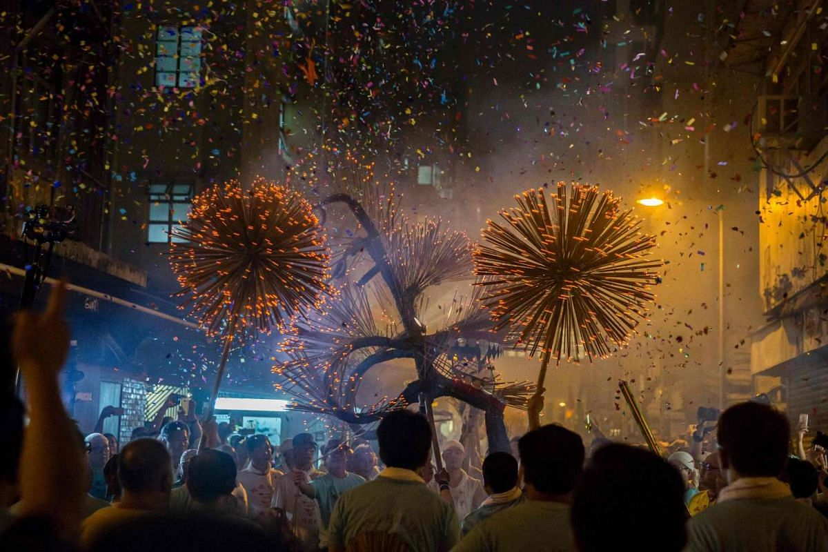 Members of the fire dragon dance team holding up the 'dragon' as it winds through the narrow streets and houses during the Tai Hang Fire Dragon Dance in Hong Kong on September 14, 2016. PHOTO: AFP