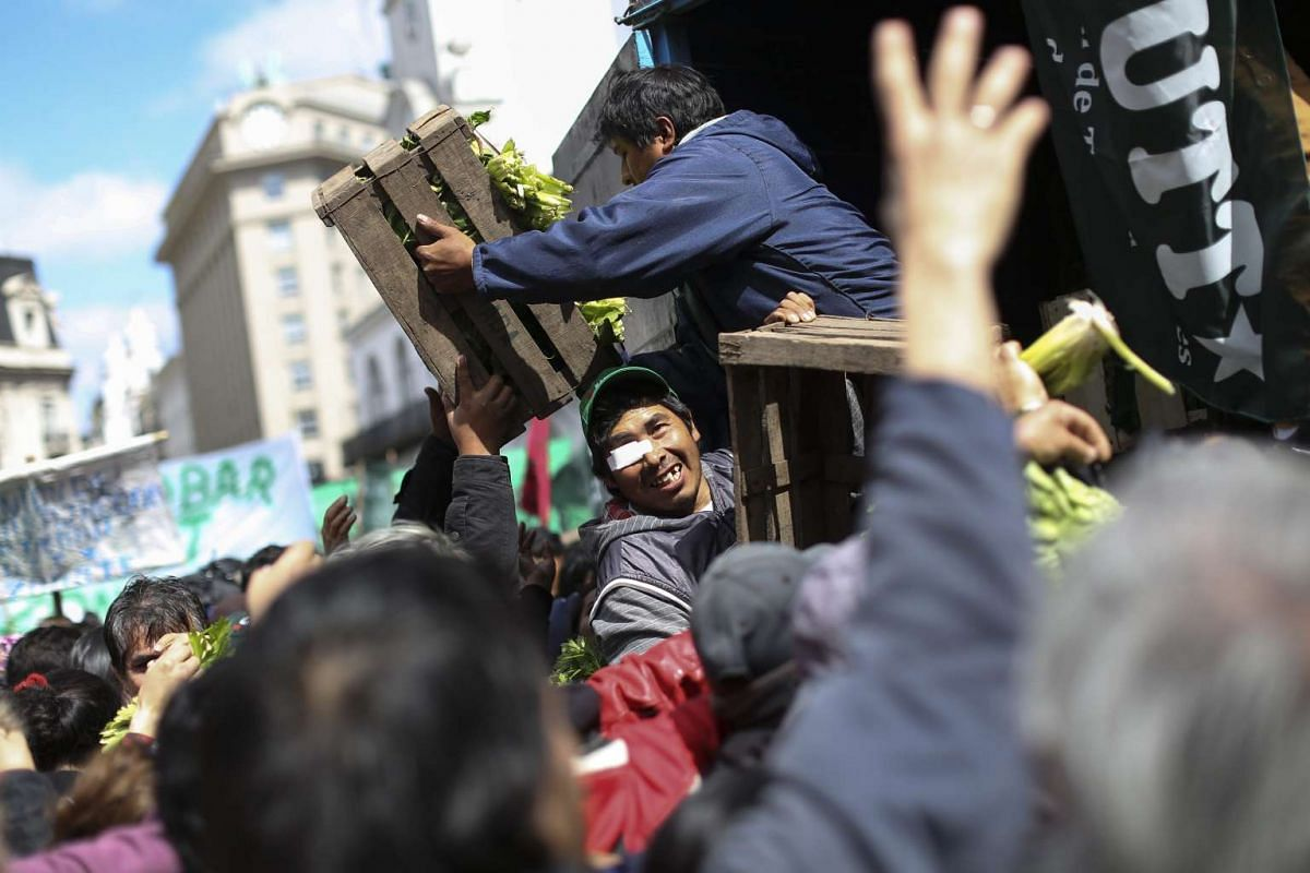 Members of farmers' unions demonstrate by donating close to 20,000 kilos of vegetables to people during a protest in front of the Government Palace in Buenos Aires, Argentina, September 14, 2016. PHOTO: EPA