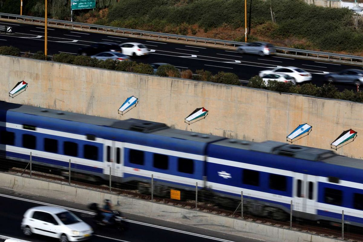 Graffiti of coffins covered in Palestinian and Israeli flags is seen on a wall running along the Ayalon highway in Tel Aviv, Israel September 14, 2016. PHOTO: REUTERS