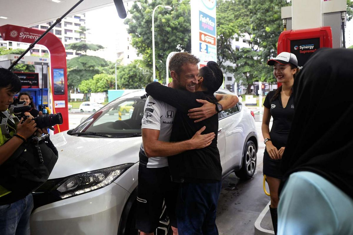 "Formula One ace Jenson Button hugging IT systems engineer Yasser Abdul Razak at the Esso station in Toa Payoh Lorong 2, September 14, 2016.  Mr Yasser was the winner of Esso's ""Who is Singapore's biggest McLaren-Honda fan?"" social media compe"