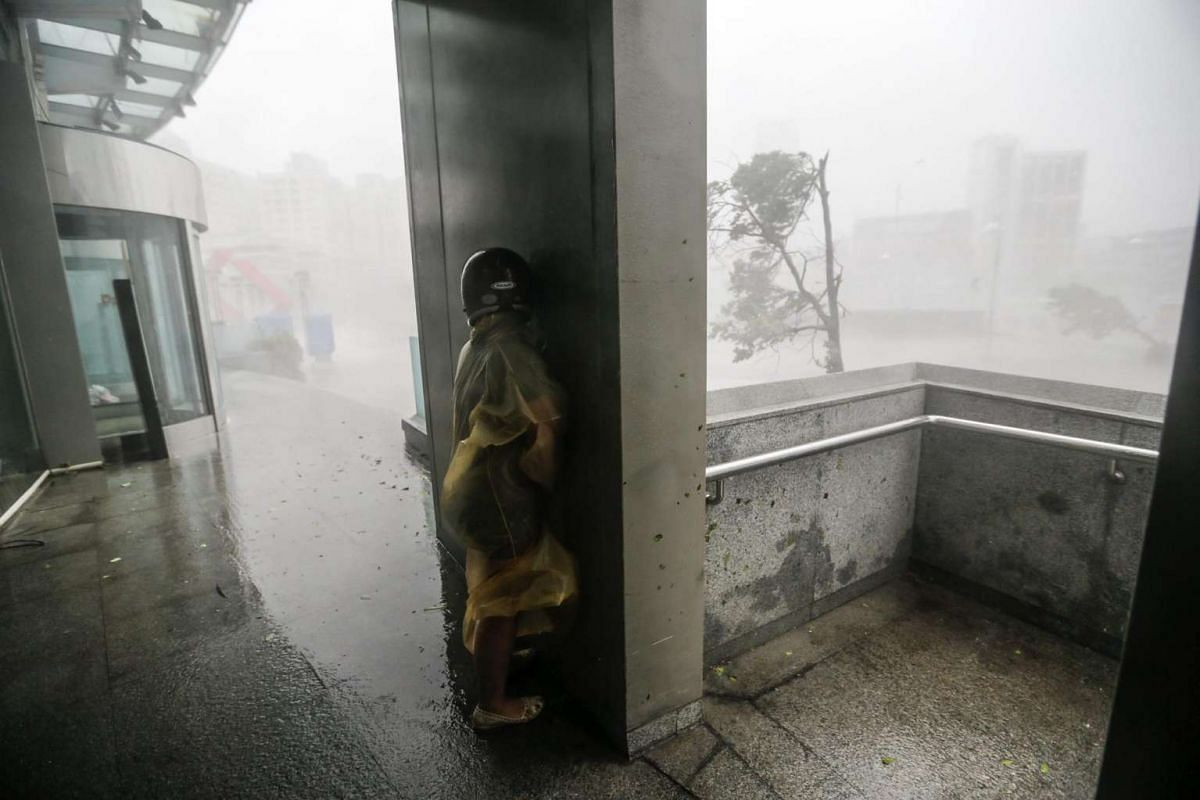 A motorist takes cover behind a wall as wind and rain from Typhoon Meranti lash Kaohsiung, southern Taiwan, on Sept 14, 2016.