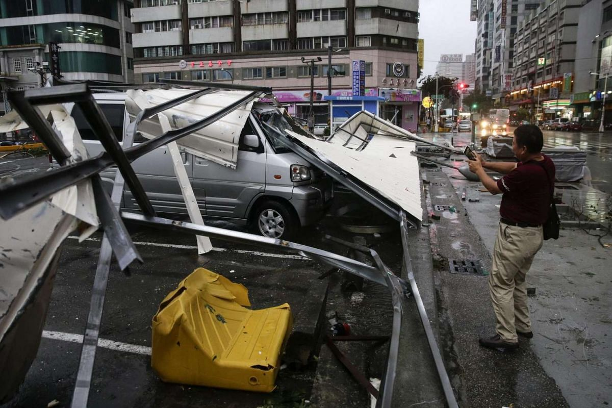 A man takes a photo of debris that fell on a car after strong winds and rain from Super Typhoon Meranti in Kaohsiung, southern Taiwan, on Sept 14, 2016.