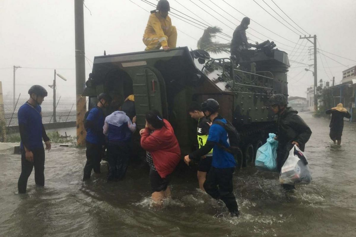 This photo by Taiwan agency CNA Photo shows residents affected by Typhoon Meranti being evacuated on a military armoured vehicle in southern Pingtung county on Sept 14, 2016.