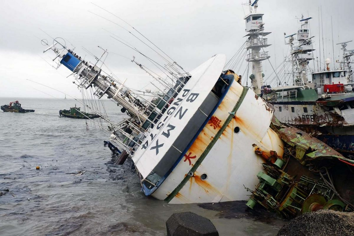 Two boats attempt to move an overturned fishing boat in the aftermath of super typhoon Meranti, at Sizihwan in Kaohsiung on Sept 15, 2016.