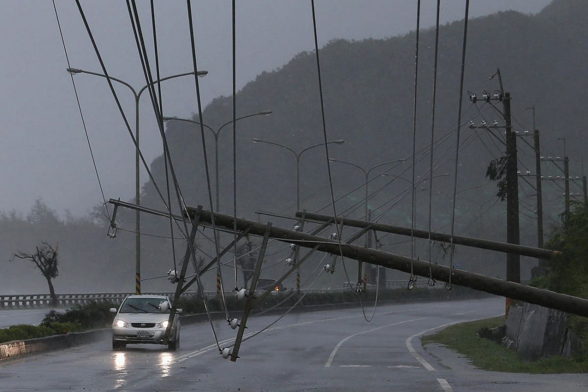 A car drives past a collapsed traffic sign, toppled by strong winds of Typhoon Meranti, in Kaohsiung, Taiwan on Sept 14, 2016.