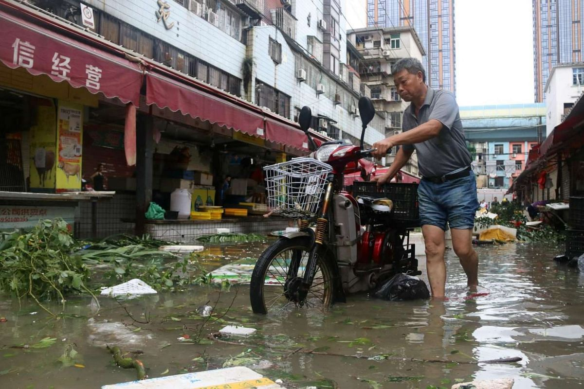 A man pushes a motorbike through a flooded street in Xiamen, in China's eastern Fujian province after Typhoon Meranti made landfall on Sept 15, 2016