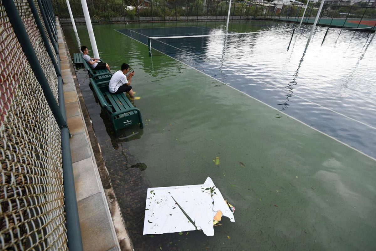 People sit on a bench inside a flooded tennis court after Typhoon Meranti makes a landfall on southeastern China, in Xiamen, Fujian province, China, on Sept 15, 2016