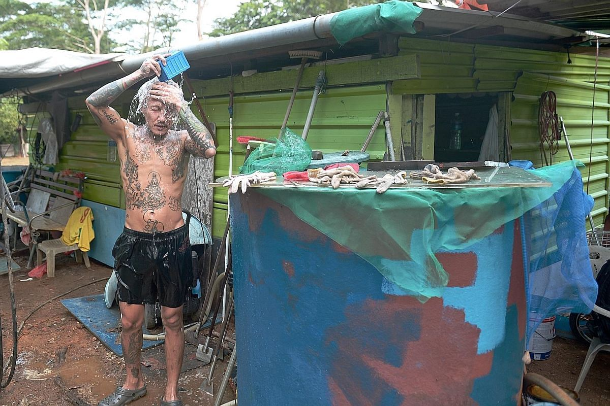 Right: Mr Massang paints the hull of a bumboat. Painting can begin only after the tide has completely receded. The boat will then be left to dry and will be ready for use the following day. Left: Mr Zainal and Mr Massang take a rare break while waiti