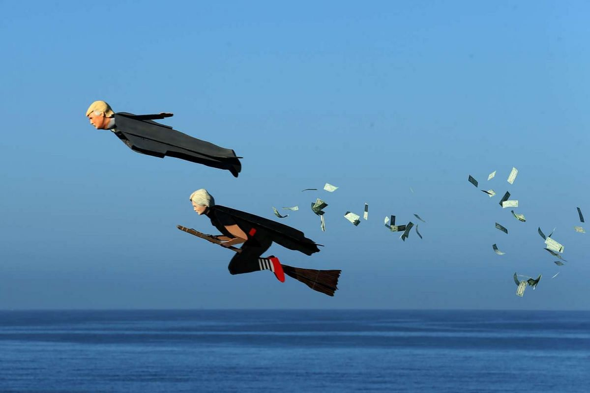 Model plane builder Otto Dieffenbach III makes his remote control plane resembling U.S. Presidential candidate Donald Trump release fake money as it flies over the beach next to a similar plane resembling Hillary Clinton in Carlsbad, California, U.S.