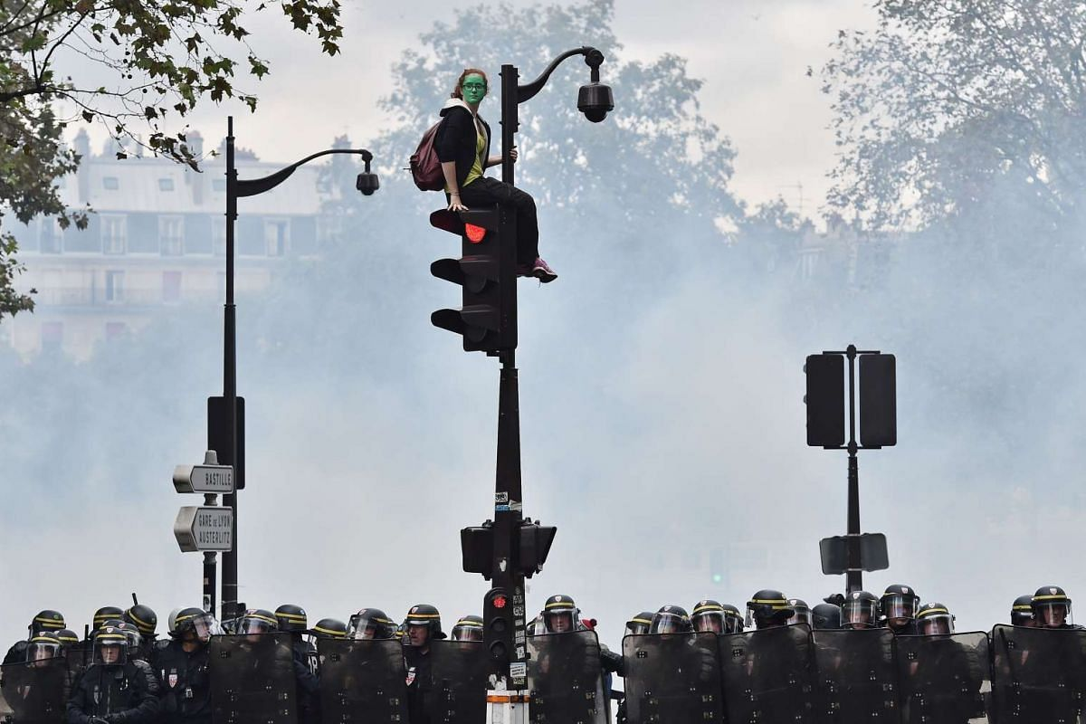 A demonstrator with her face painted in green, sits on a traffic light as French riot police secure the area during a protest against the controversial labour reforms of the French government in Paris on September 15, 2016. PHOTO: AFP