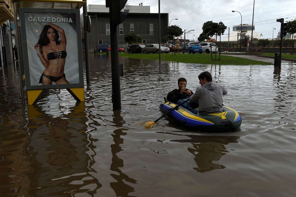 A man rows an inflatable raft after heavy rains flooded downtown of Aviles, Spain, September 15, 2016. PHOTO: REUTERS