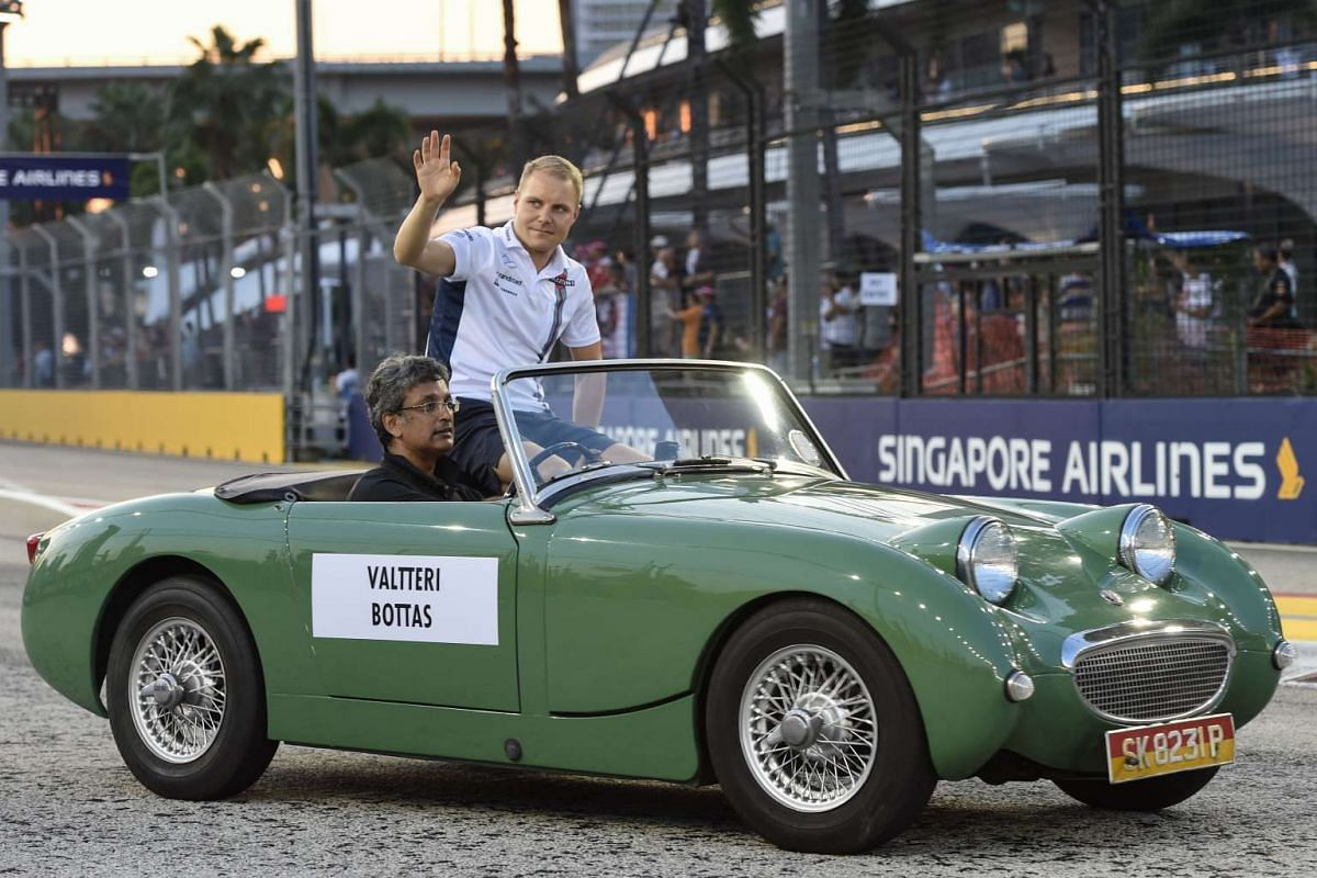 Finnish driver Valtteri Bottas waves to the crowd during the driver's parade before the 2016 Formula One Singapore Airlines Singapore Grand Prix on Sept 18, 2016.