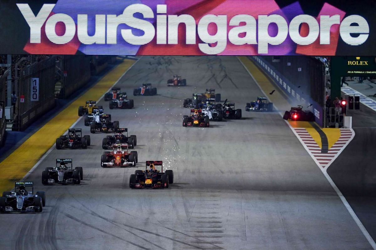 German driver Nico Rosberg (left) leads the start of the race, as German driver Nico Hulkenberg (right) crashes during the 2016 Formula One Singapore Airlines Singapore Grand Prix on Sept 18, 2016.