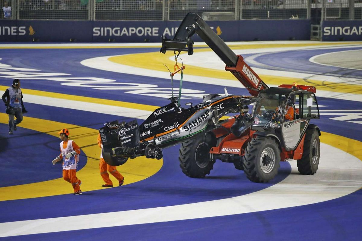 A crane lifts Nico Hulkenberg's car after he crashed into a wall during the 2016 Formula One Singapore Airlines Singapore Grand Prix on Sept 18, 2016.