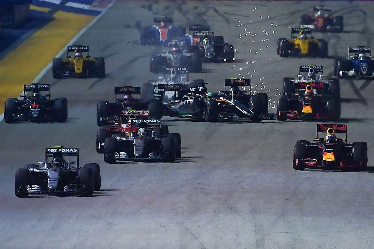 German driver Nico Rosberg (left) leads the race as German driver Nico Hulkenberg (centre) crashes during start of the 2016 Formula One Singapore Airlines Singapore Grand Prix on Sept 18, 2016.
