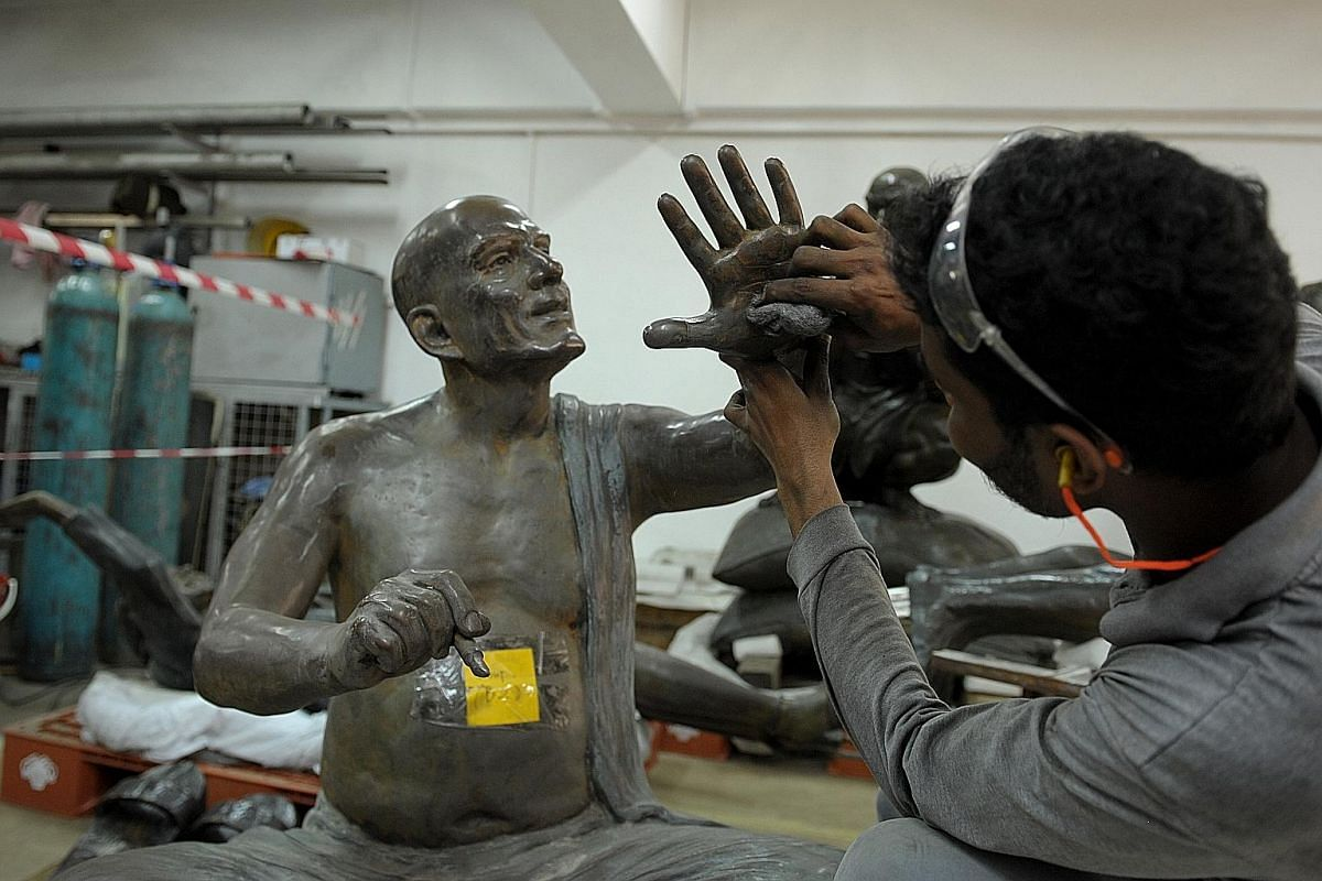 Mr Mofijul Mahhamed, 28, a craftsman from Singapore metalworks company Metalworld, using soft steel wool to remove green patina from a piece of the sculpture called From Chettiars To Financiers.