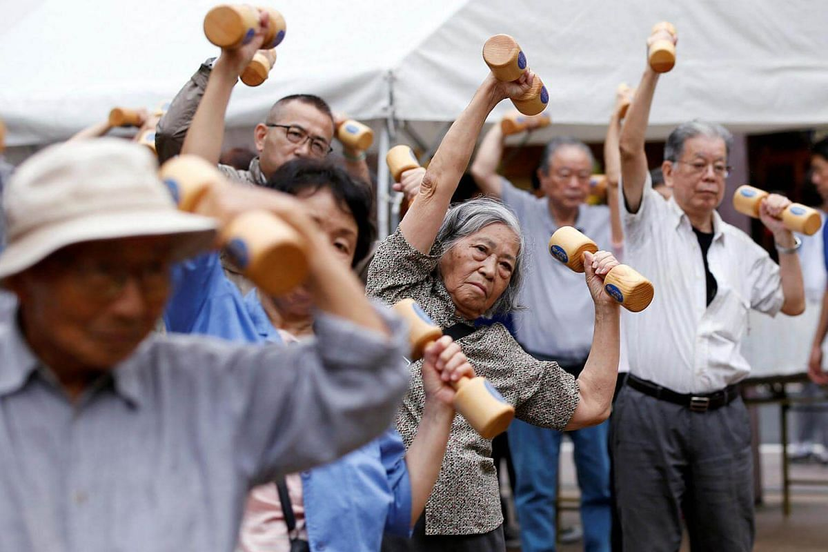 """Elderly and middle-aged people exercising with wooden dumbbells during a health promotion event to mark Japan's """"Respect for the Aged Day"""" at a temple in Tokyo's Sugamo district, Japan, on Sept 19, 2016."""