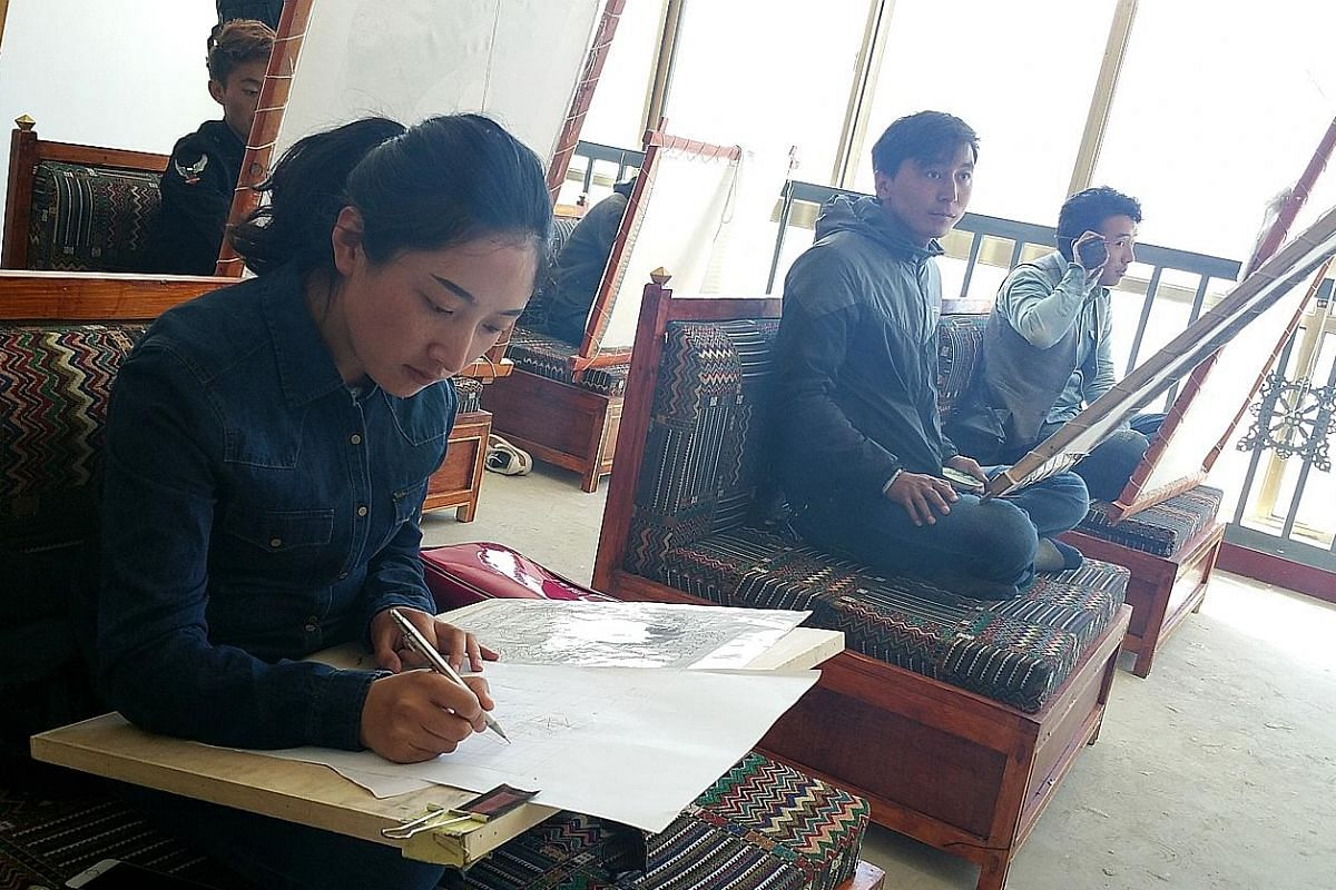 Members of Lhasa Pureland Football Club, recognised as China's highest-altitude football club. Ms Donglai (right) of Tanbaramdan Thangka Art School, which has around 80 students learning the art form.