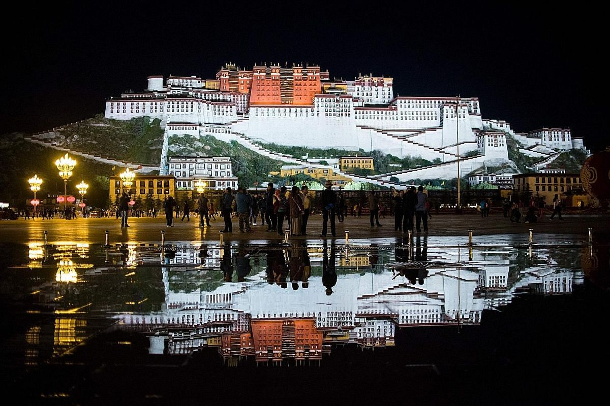 A souvenir peddler at the Lulang Forest viewing platform located 80km from the southern Tibetan city of Nyinchi. Tourists viewing the iconic Potala Palace in Lhasa, the capital city of the autonomous region of Tibet. The palace, built by the fifth Da