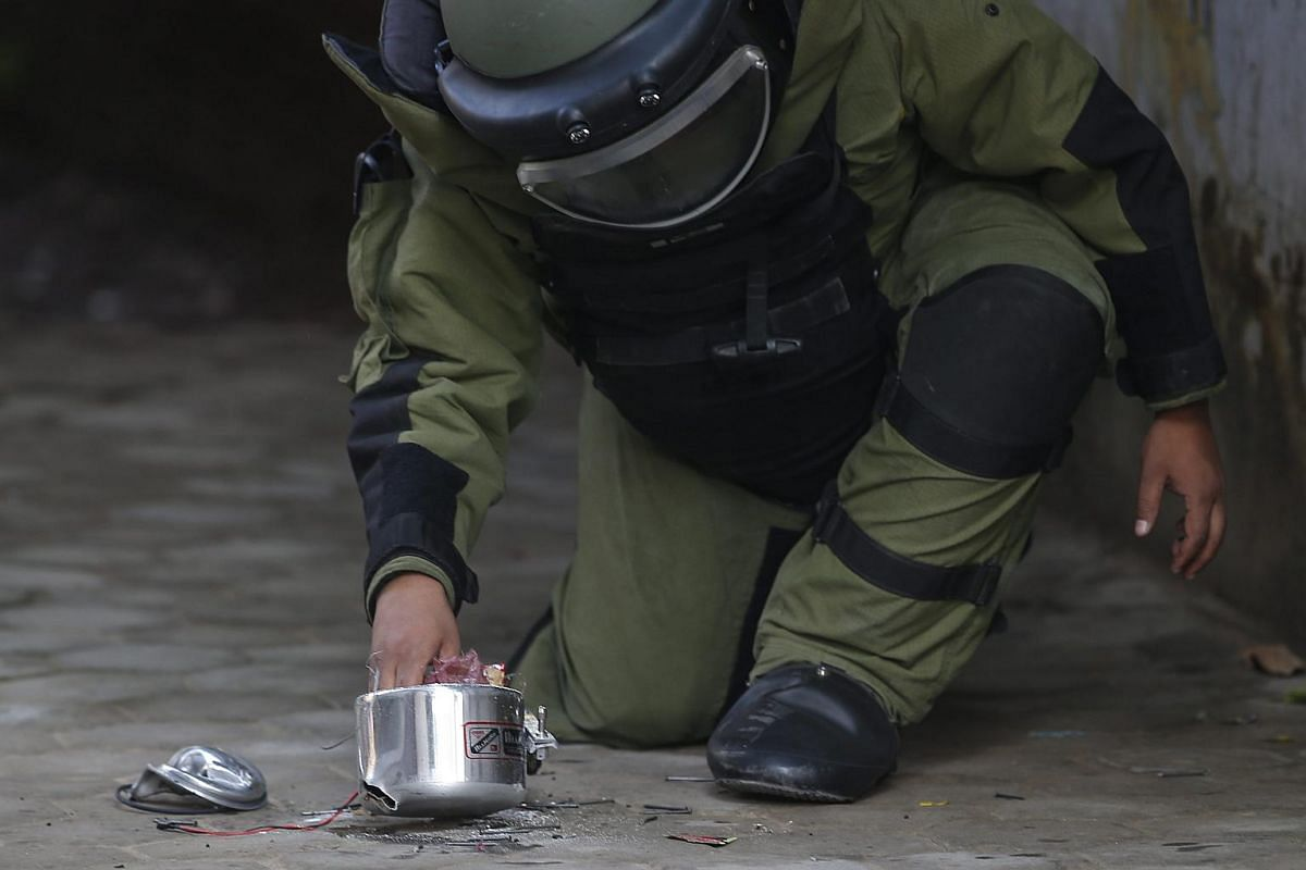 A Nepalese armed police force member wearing a bomb disposal suit attempts to disarm a suspected bomb planted near the Kanchanjangha Intergrated Model school area in Kathmandu, Nepal on Sept 20, 2016.