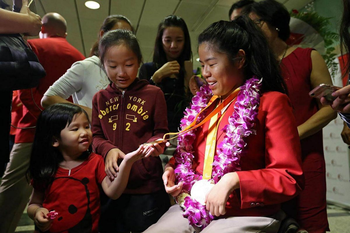 Singapore's Paralympic double gold medallist Yip Pin Xiu shows her medals to her nieces Shernice Ang (left), four, and Chew Xiu Wen, 10, upon arriving at Changi Airport.