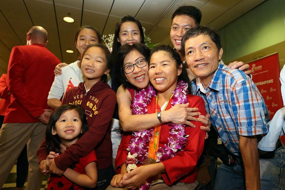 Singapore's Paralympic double gold medallist Yip Pin Xiu poses for a photograph with her family members upon arriving at Changi Airport.