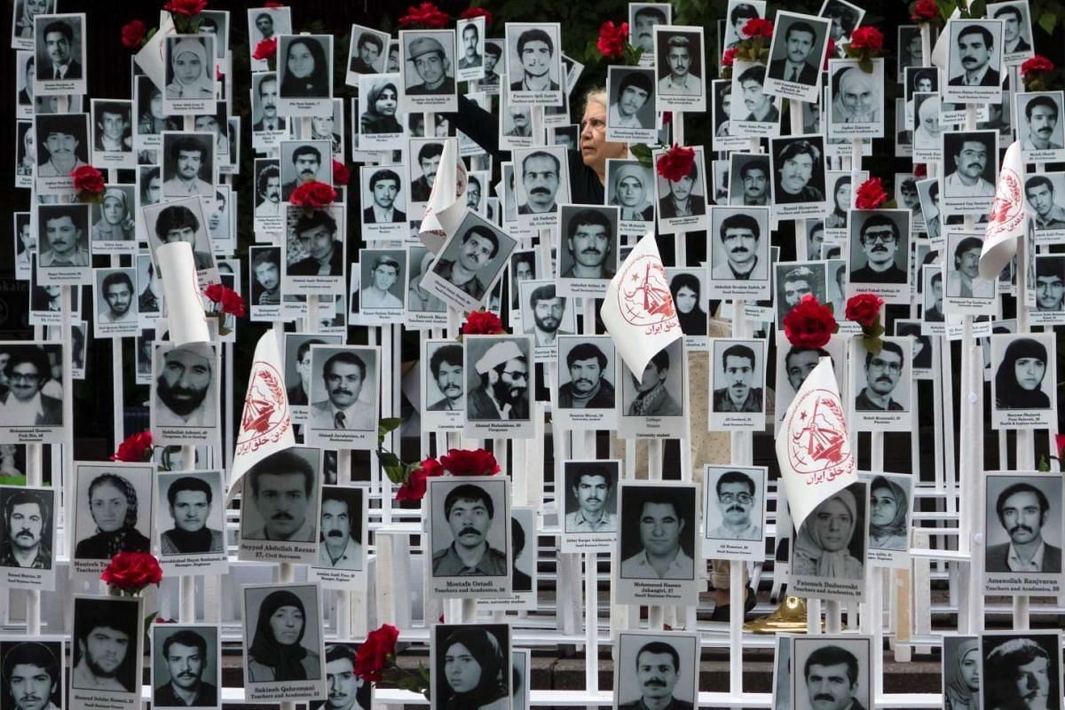 A woman places flowers on photographs of 4,000 of the 30,000 political prisoners who protesters claimed have been executed by the Iranian regime, at a rally in Dag Hammerskjold plaza near the United Nations in New York on Sept 20, 2016.