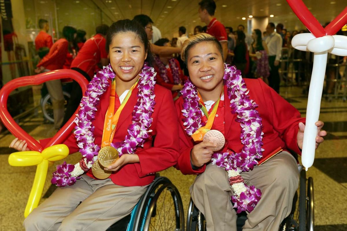 Yip Pin Xiu and Theresa Goh pose for pictures with their medals upon their arrival at Changi International Airport on Sept 21, 2016.
