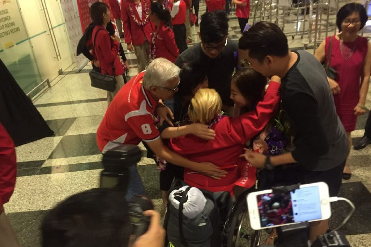 Theresa Goh shares a hug with her family upon returning home.