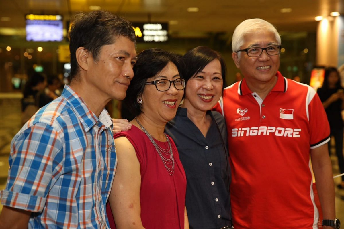 Yip Pin Xiu and Theresa Goh's parents pose for the cameras at Changi Airport.
