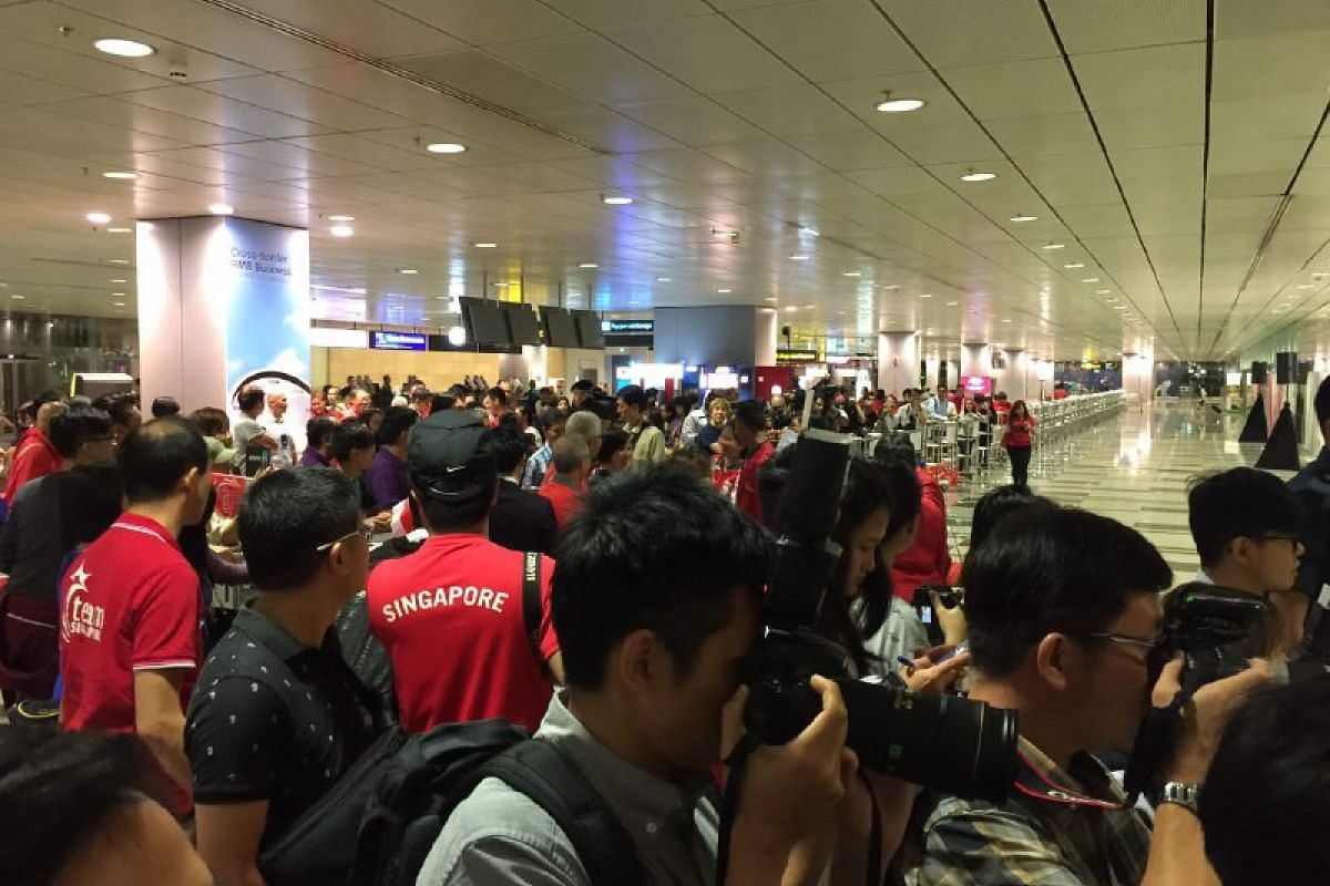 Fans and the media gather as they await Singapore's Paralympic athletes to emerge from the gate.
