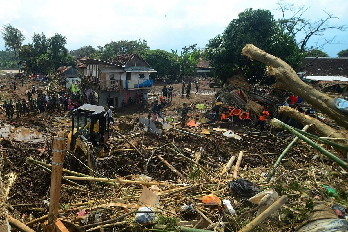 Indonesian military and rescue workers are seen as heavy equipment is used to clear away debris after a flash flood from heavy rains hit Garut, West Java, Indonesia on Sept 21, 2016.