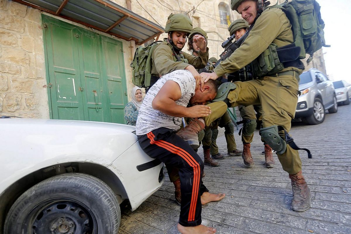 An Israeli army soldier kicks a Palestinian as he is being arrested following scuffling during raids on houses in the West Bank city of Hebron on Sept 20, 2016.