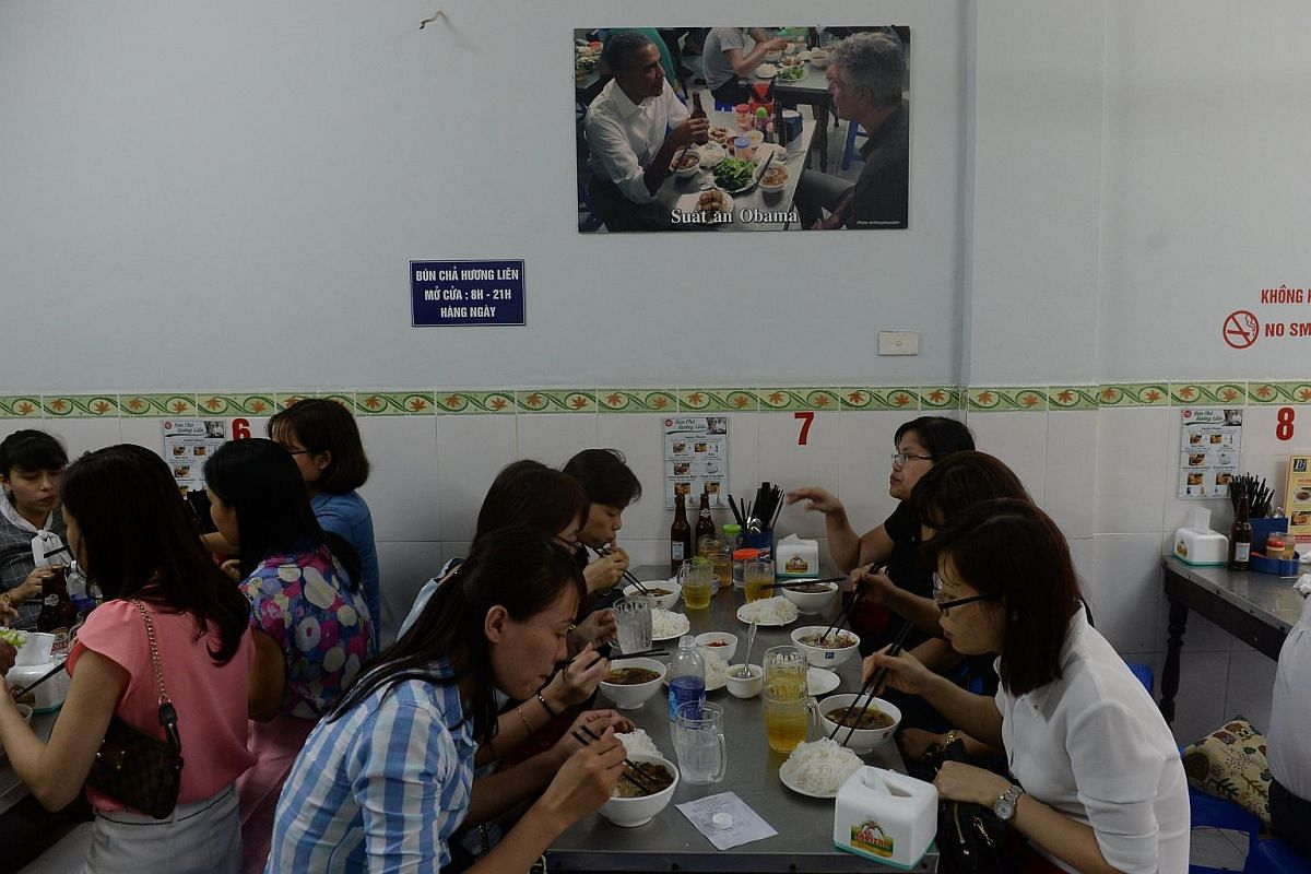 This picture taken on Sept 12, 2016 shows customers eating under a picture showing US President Barack Obama eating during his visit to the same room of the Bun Cha Huong Lien restaurant last May in Hanoi.