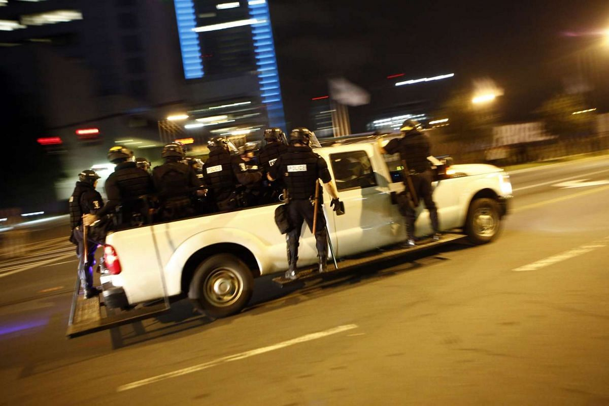 Riot police race to intercept a large group of activists attempting to block traffic on Interstate 277 as residents and activists protest the death of Keith Scott on Sept 22, 2016 in Charlotte, North Carolina.