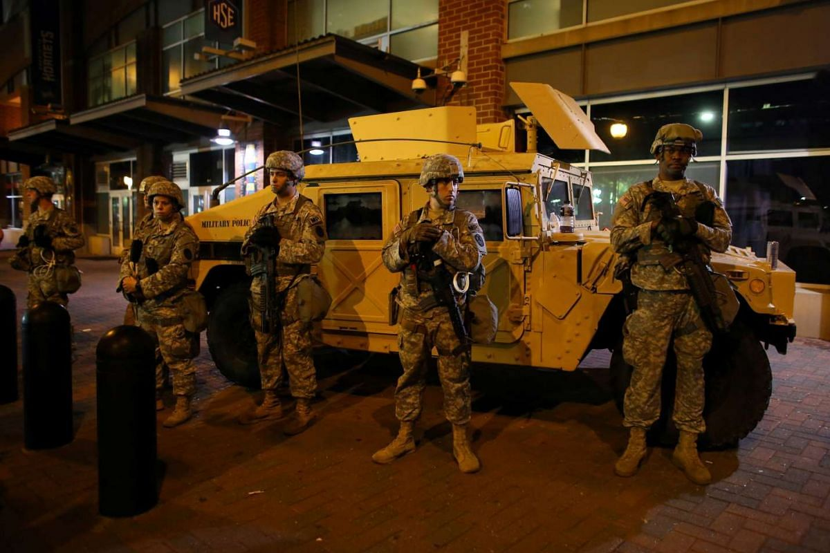 US National guard troops keep watch downtown as residents and activists protest the death of Keith Scott on Sept 22, 2016 in Charlotte, North Carolina.
