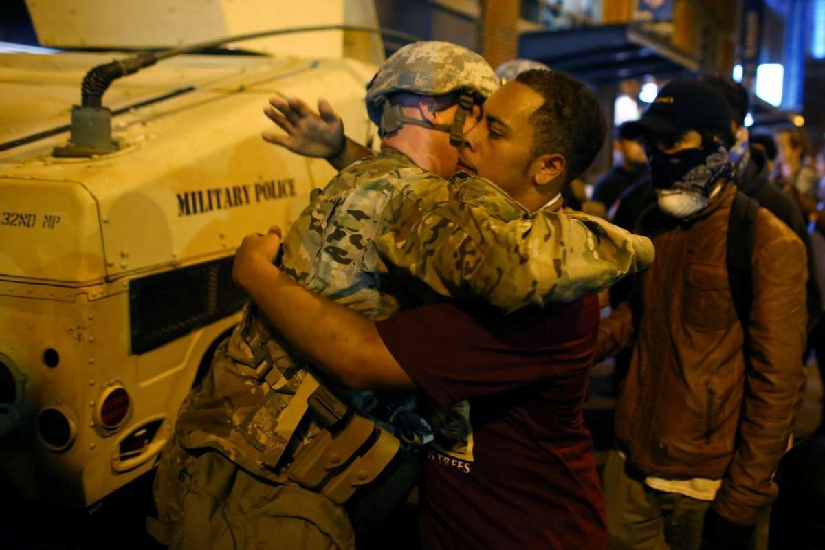 A US National guard soldier accepts a hug from protester  as residents and activists protest the death of Keith Scott on Sept 22, 2016 in Charlotte, North Carolina.