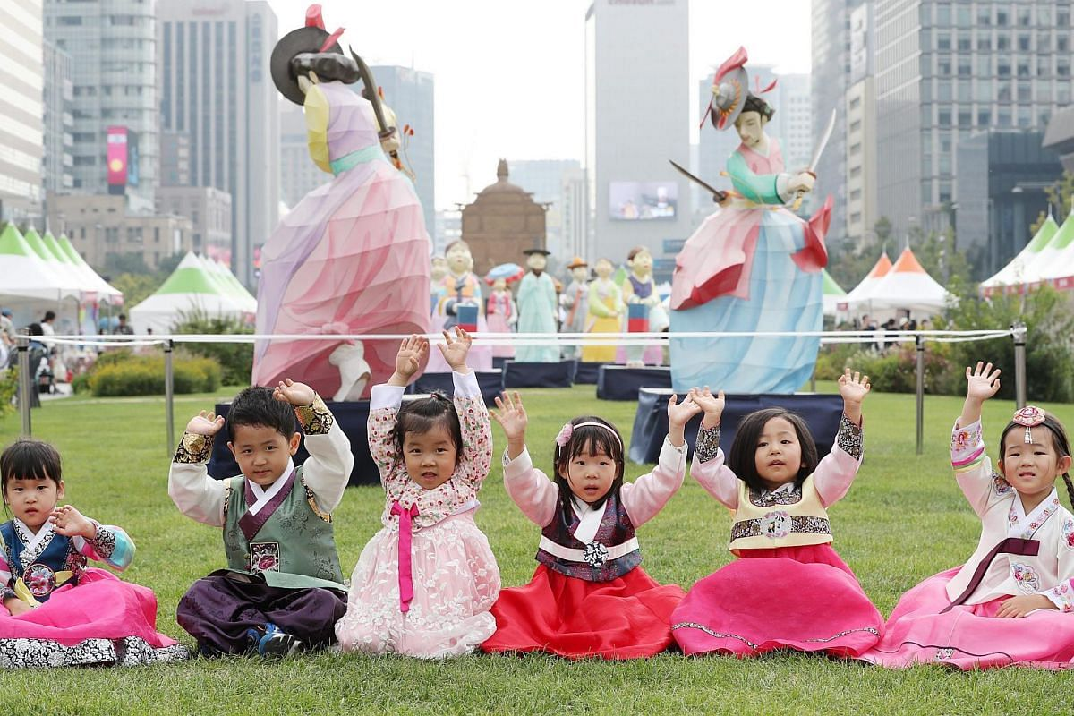 """Children clad in South Korea's traditional costume, called """"hanbok"""", wave during a hanbok festival at a square in downtown Seoul, South Korea on Sept 23, 2016, which was held as part of a hanbok festival that opened on the same day for a three-day ru"""