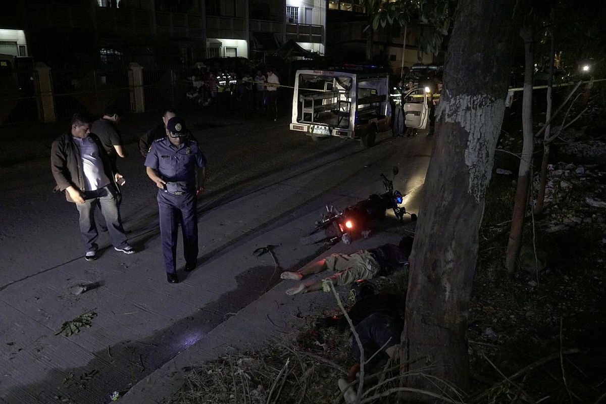 Filipino police investigators examine bodies of suspected drug dealers, who was shot dead during a police operation against illegal drugs in Pasig city, east of Manila, Philippines on Sept 23, 2016.