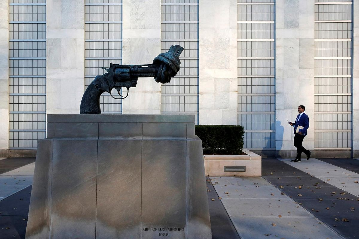 """A man walks by the """"Non-Violence"""" sculpture by Swedish artist Carl Fredrik Reutersward at the United Nations headquarters during the 71st Session of the United Nations General Assembly in Manhattan, New York on Sept 22, 2016."""