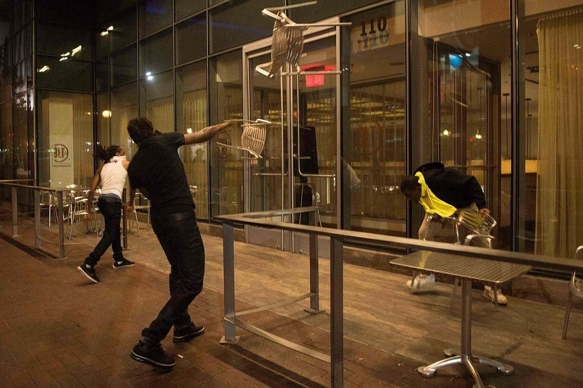 Protesters throw chairs at a restaurant as residents and activists protest the death of Keith Scott on Sept 21, 2016 in Charlotte, North Carolina.