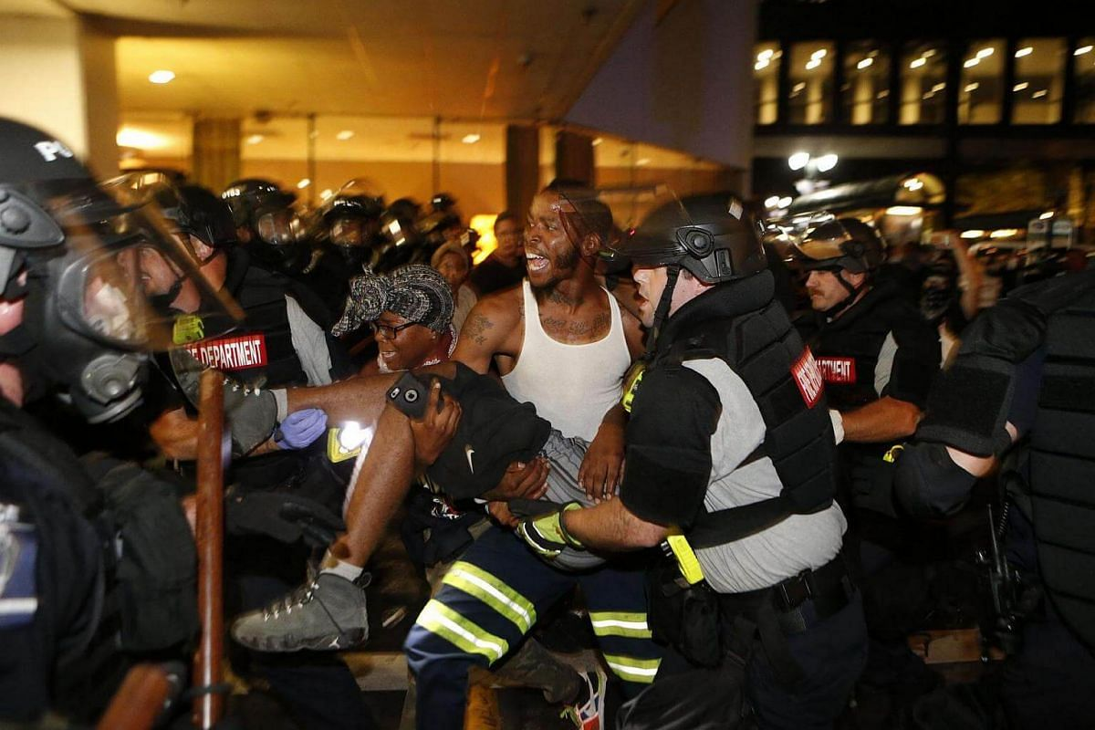 Police and protesters carry a seriously wounded protester into the parking area of the the Omni Hotel as residents and activists protest the death of Keith Scott on Sept 21, 2016 in Charlotte, North Carolina.