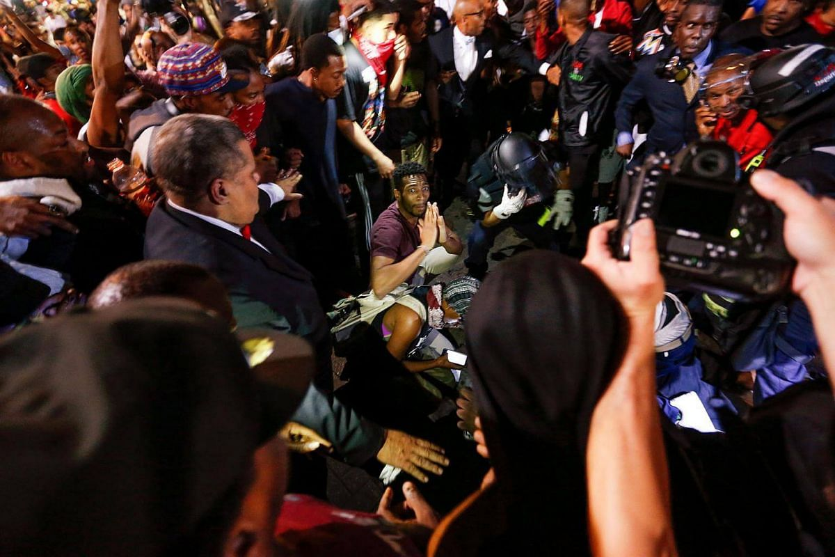 People surround a shooting victim as residents and activists protest the death of Keith Scott on Sept 21, 2016 in Charlotte, North Carolina.