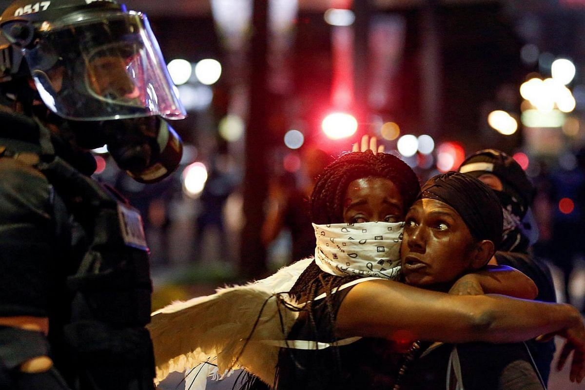 Two women embrace while looking at a police officer as residents and activists protest the death of Keith Scott on Sept 21, 2016 in Charlotte, North Carolina.