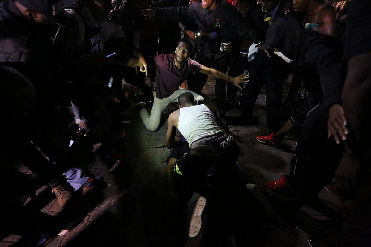 A young man is attended to as he lies on the sidewalk after being shot in front of the Omni Hotel as residents and activists protest the death of Keith Scott on Sept 21, 2016 in Charlotte, North Carolina.