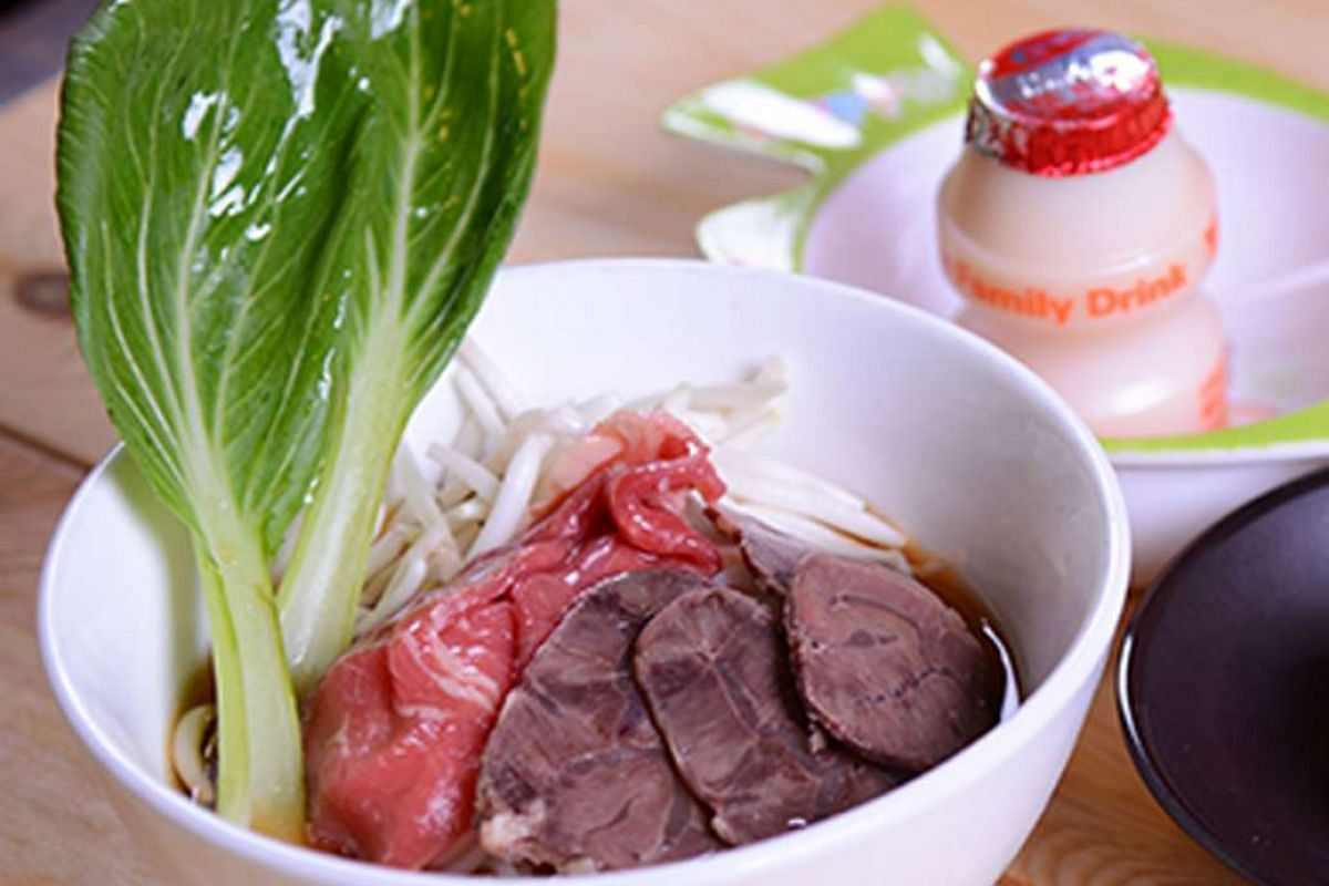 Hock Lam beef noodle bowl with ribeye and brisket slices, a mantou and a bottle of Yakult.